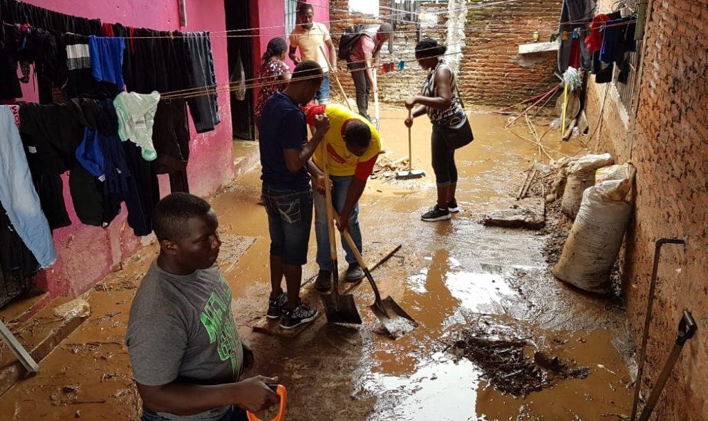 Migrantes centroamericanos y extra continentales ayudan en limpieza en viviendas y calles afectadas por la lluvia